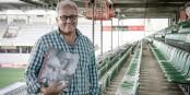"""Fritz Keller mit dem Fotobuch """"Die Grenzgänger"""" im Freiburger Stadion. Foto: © Pressebüro Arne Bicker"""