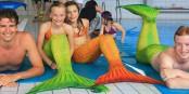 Meerjungfrauen und Wassermänner beim Mermaiding-Schwimmkurs der PH Freiburg im Westbad (rechts im Bild Schwimmtutor Nicholas Frank). Foto: PH Freiburg.