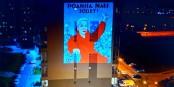 """"""" Macha, la Patrie t'appelle"""" : détournement d'une affiche russe par l'artiste bélarusse Ania Redko, projetée sur un immeuble de Minsk. Elle montre Maria Kalesnikava avec son passeport déchiré   Foto: Nexta/CC-BY-SA/4.0Int"""